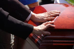 hands on a casket at a funeral